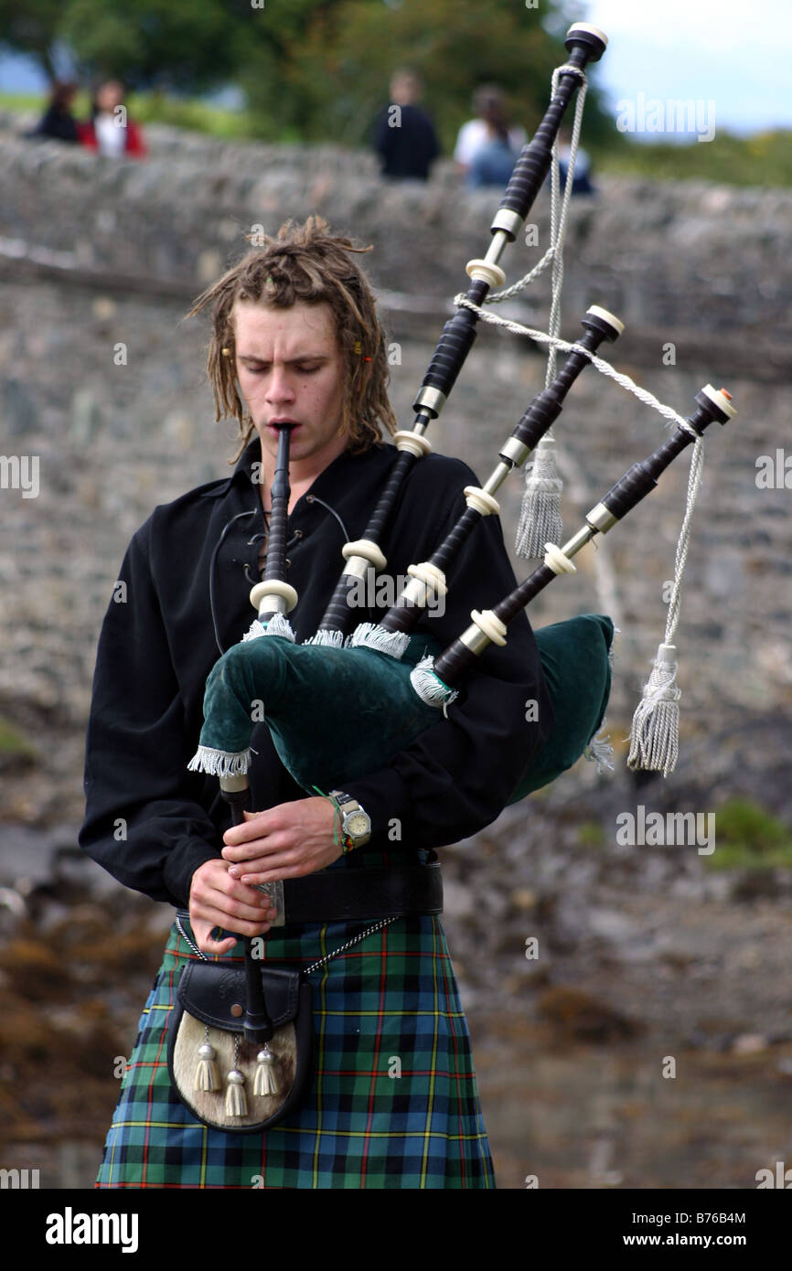 Traditional Man in Kilt, Bagpiper in Scottish Highlands with bagpipes at Eilean Donan Castle - Stock Image