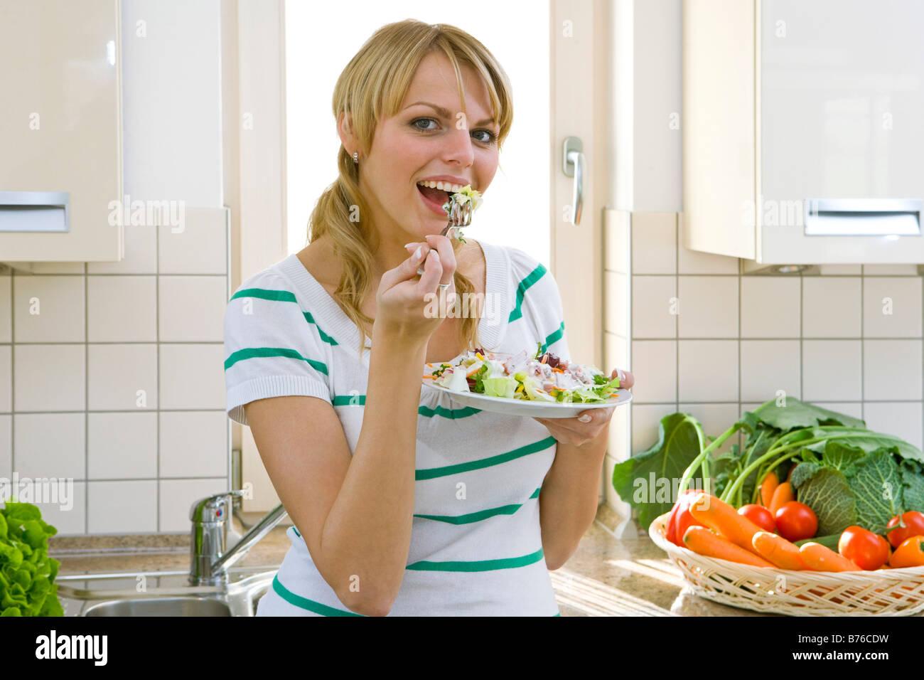 Frau isst Salat, woman eating salad - Stock Image