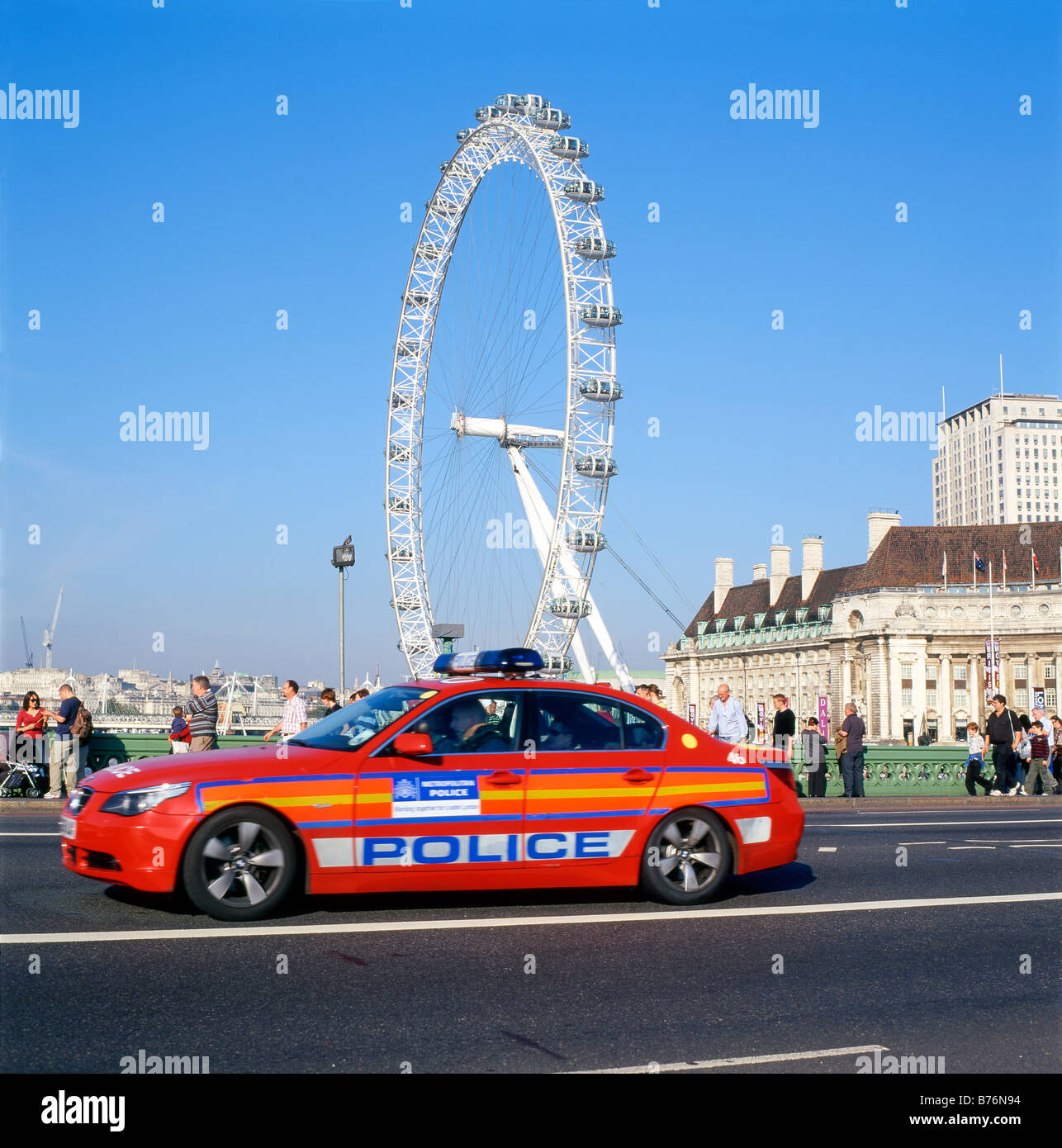 The London Eye And A Red London Metropolitan Police Car Crossing  Westminster Bridge England UK