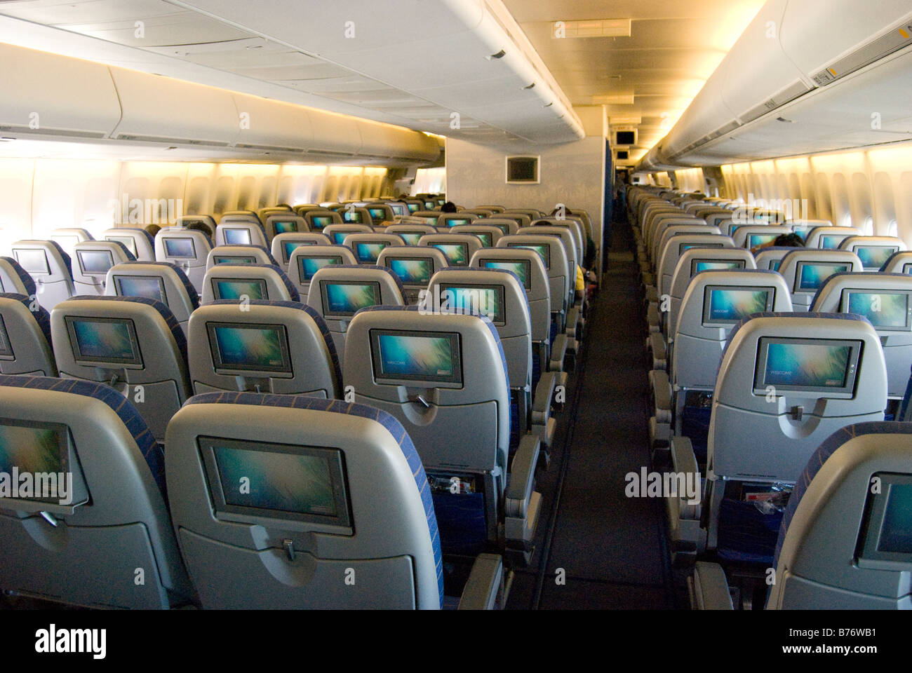interior view of air philippines boeing 747 jumbo jet showing seats with entertainment screens stock