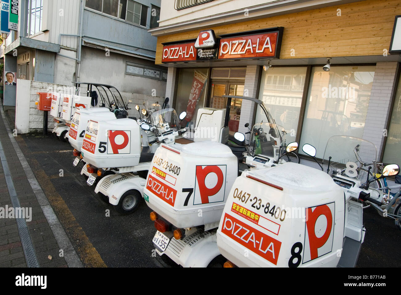 pizza delivery motorcycles parked near pizzeria,Japan - Stock Image