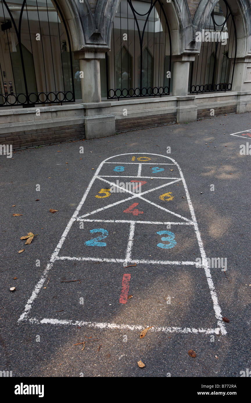 A hop scotch grid painted on a playground - Stock Image