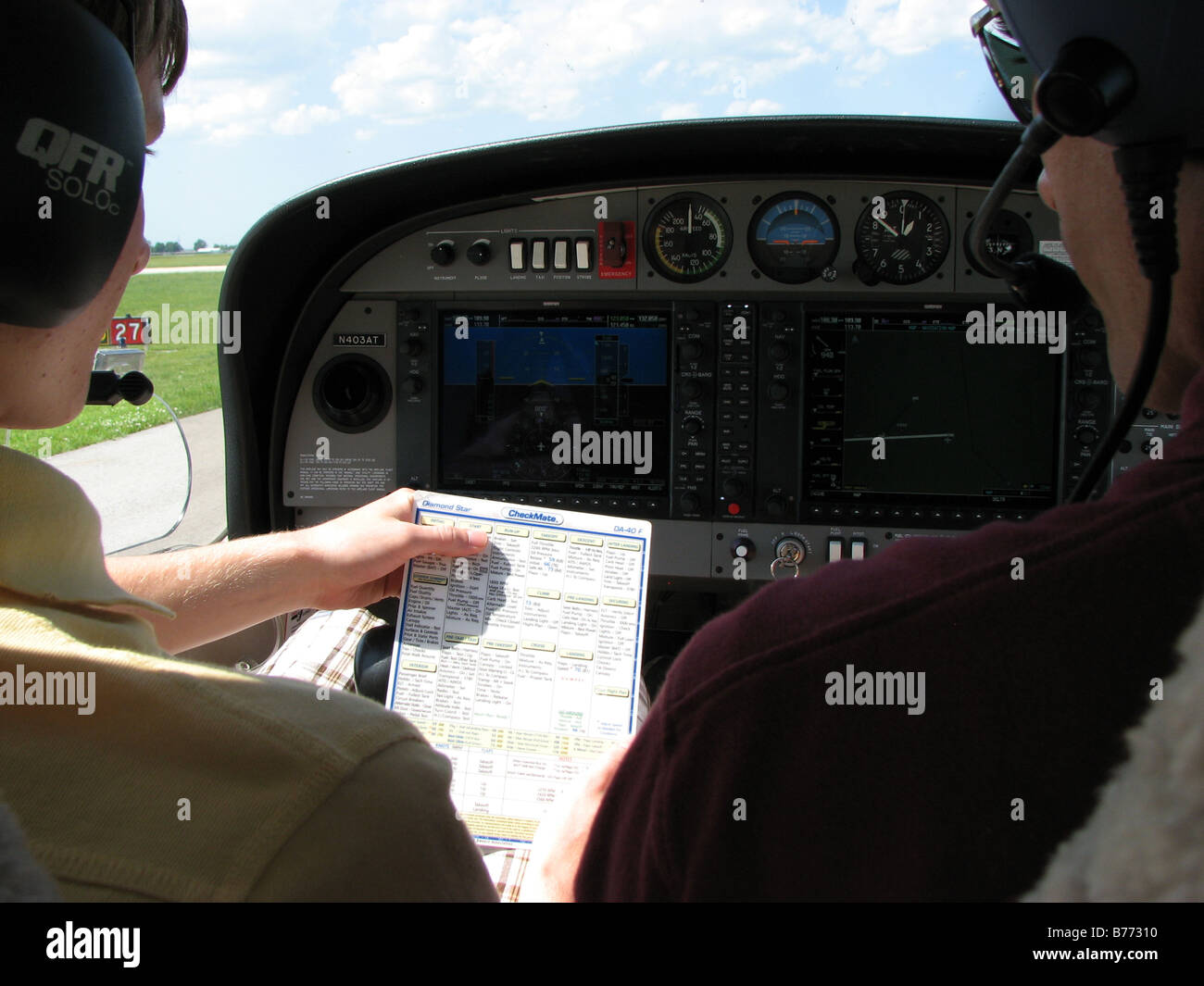Pilot and co-pilot reviewing checklist before takeoff. - Stock Image