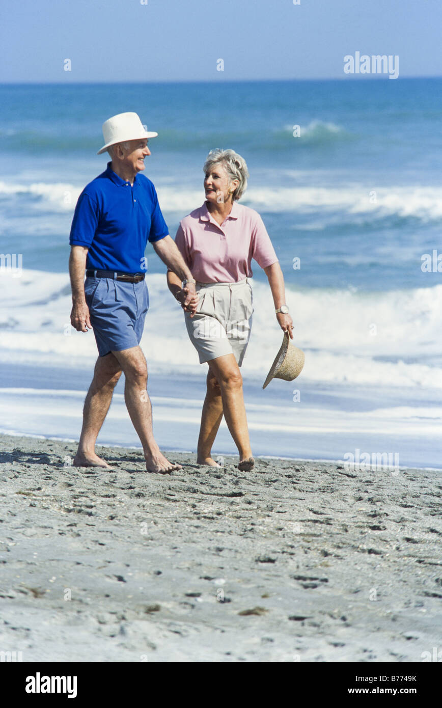 Seniors relaxing together, walking on beach, Miami - Stock Image