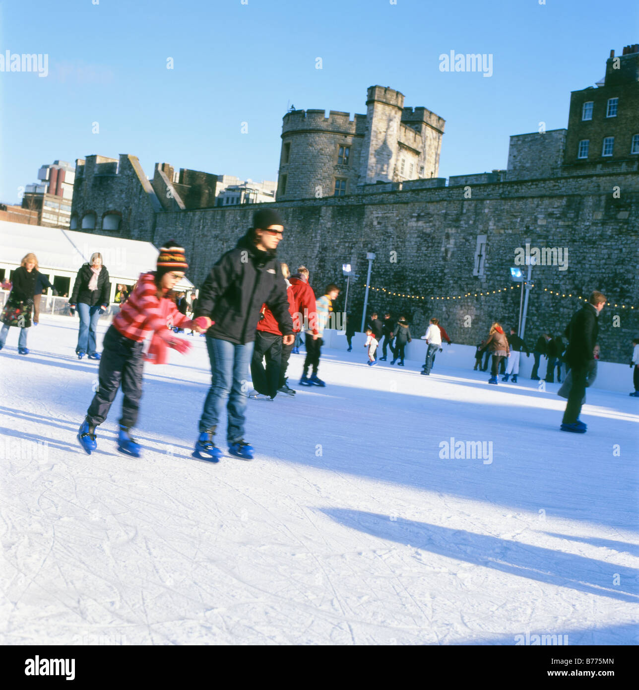 People ice skating at Christmas on the Tower of London ice rink  London England UK  KATHY DEWITT - Stock Image