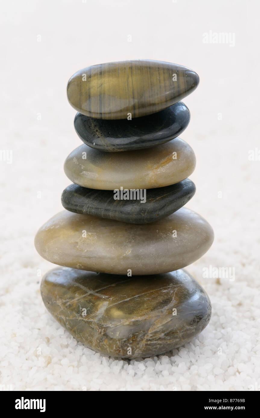 Stack of balanced polished rocks on white quartz pebbles to aid Zen contemplation - Stock Image