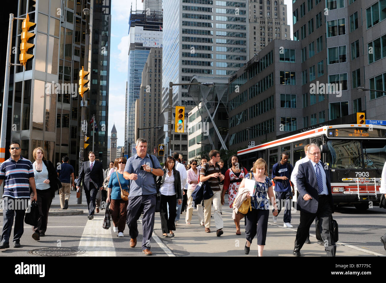 Commuters rushing to transit at the end of a busy Toronto work day, looking north along Bay Street from the south - Stock Image