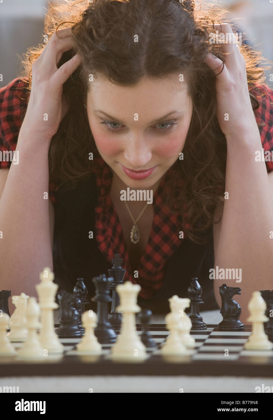 Close up of woman looking down chessboard - Stock Image