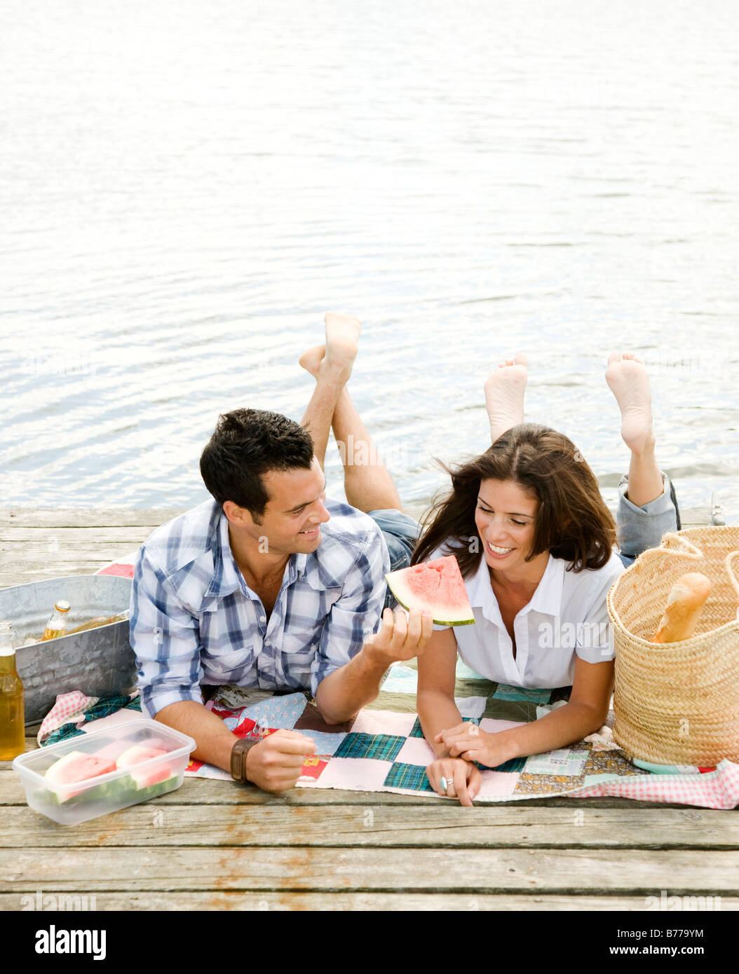 Couple picnicking on dock - Stock Image