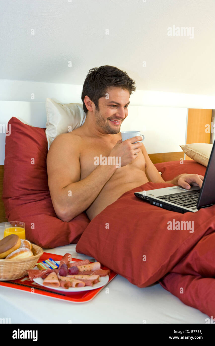 Mann Mit Laptop Fruehstueckt Im Bett Man With Laptop Has Breakfast