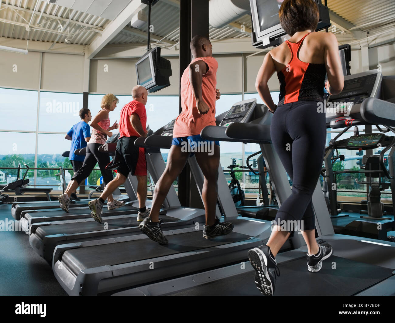 Men and women running on treadmills - Stock Image