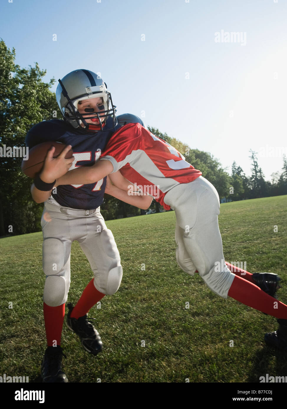 Football player tackling opponent - Stock Image