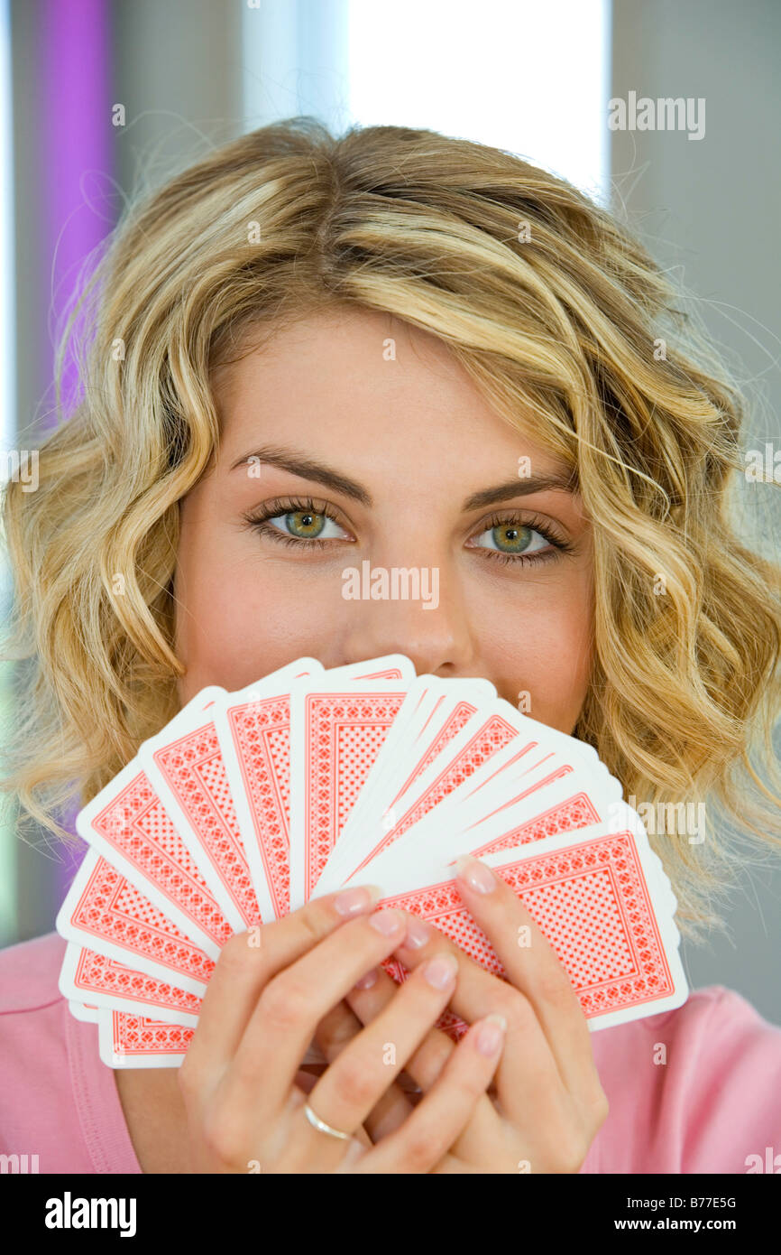 retty young woman playing cards, Poker Face - Stock Image