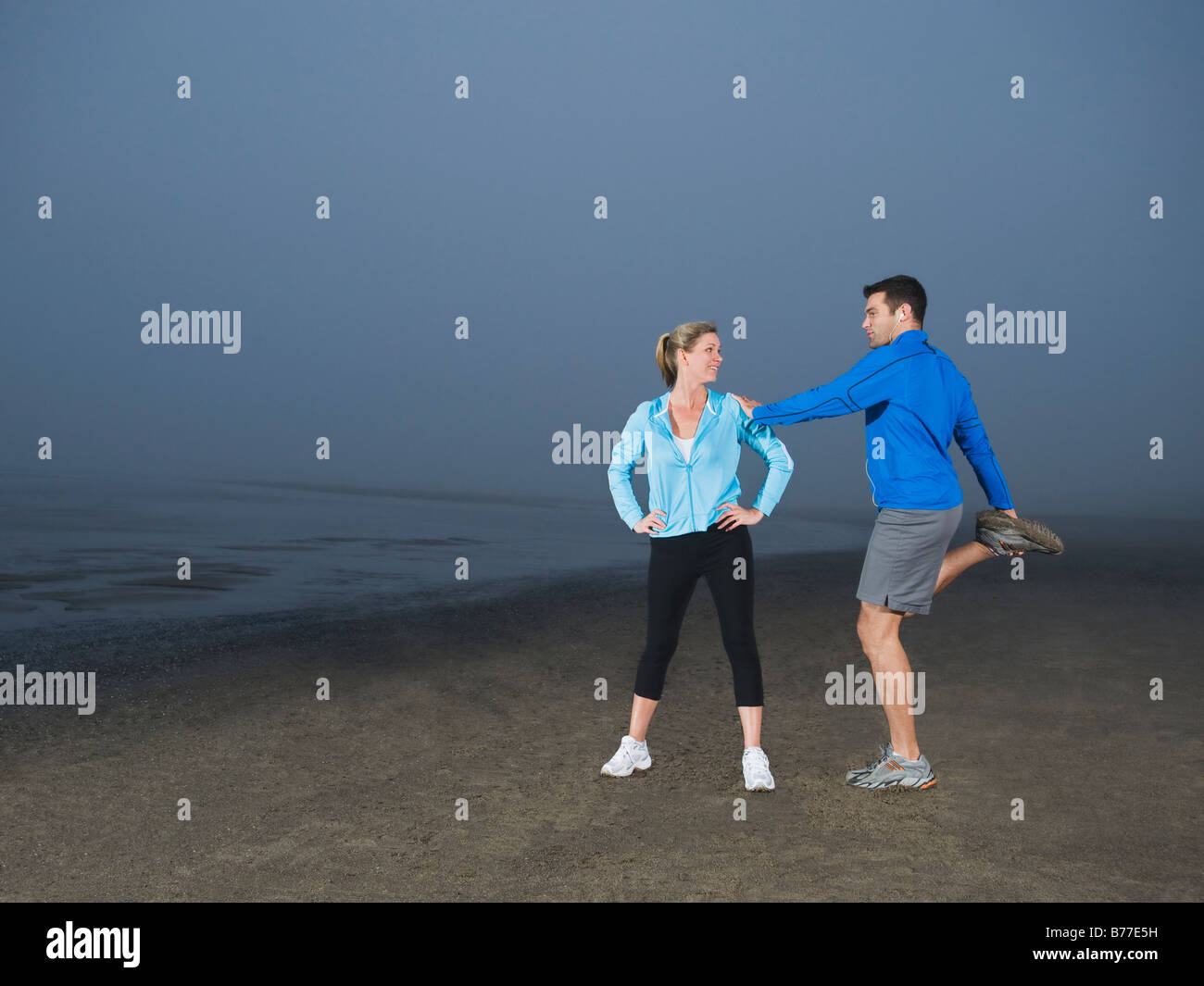 Couple stretching on beach - Stock Image