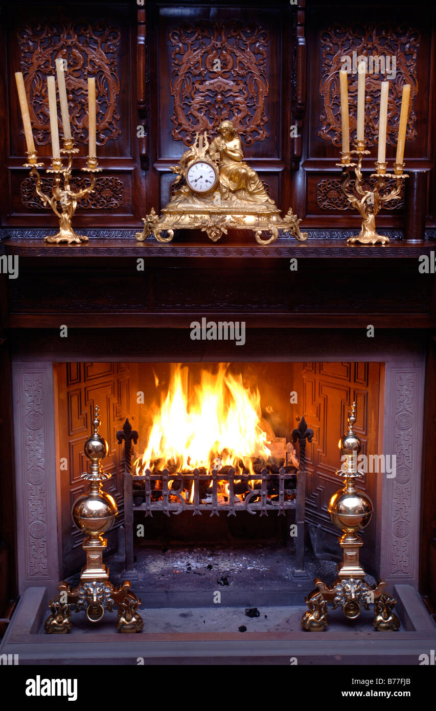 AN OPEN FIRE IN A COUNTRY HOUSE WITH AN ORIENTAL CARVED WOOD