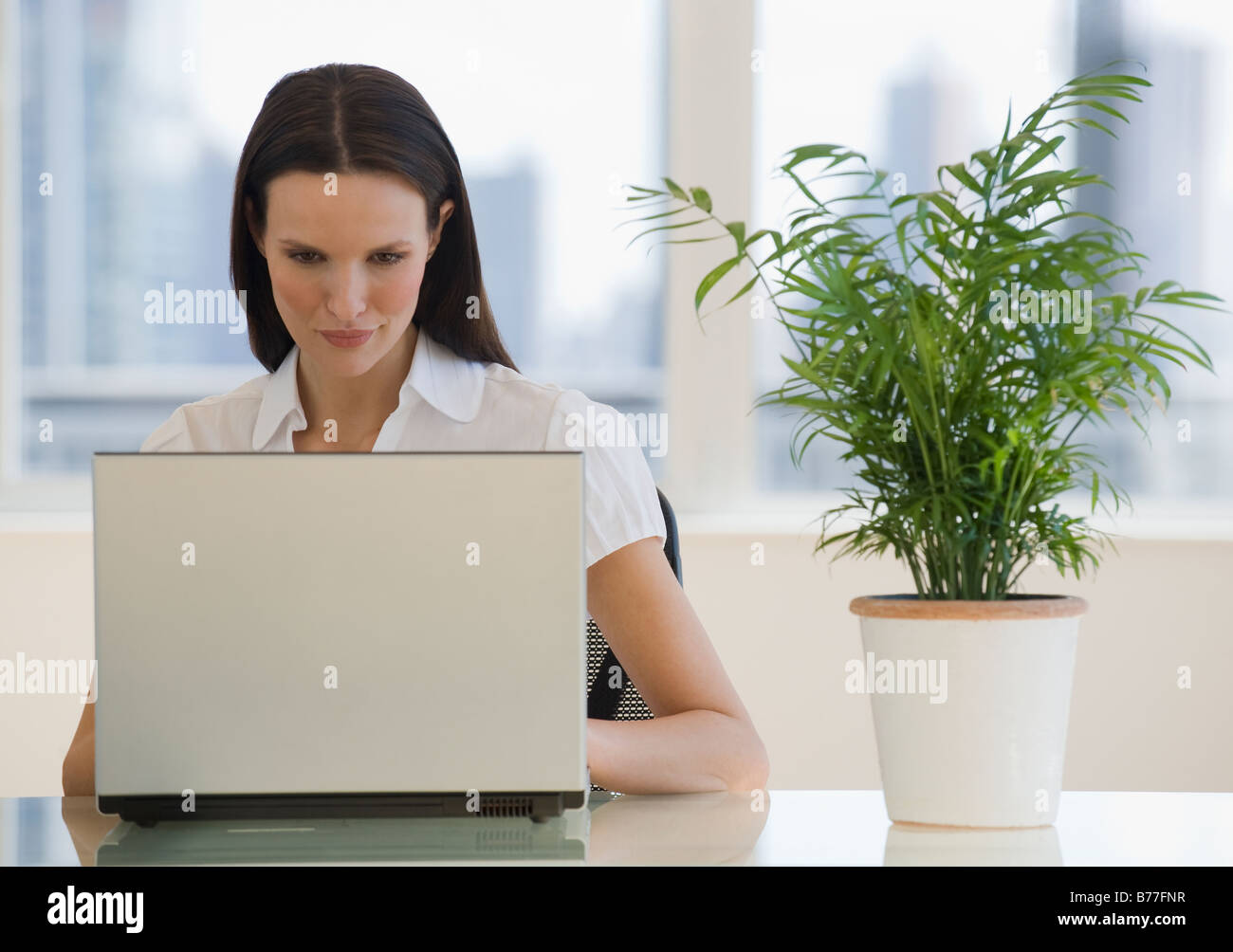 Businesswoman working on laptop next to plant - Stock Image