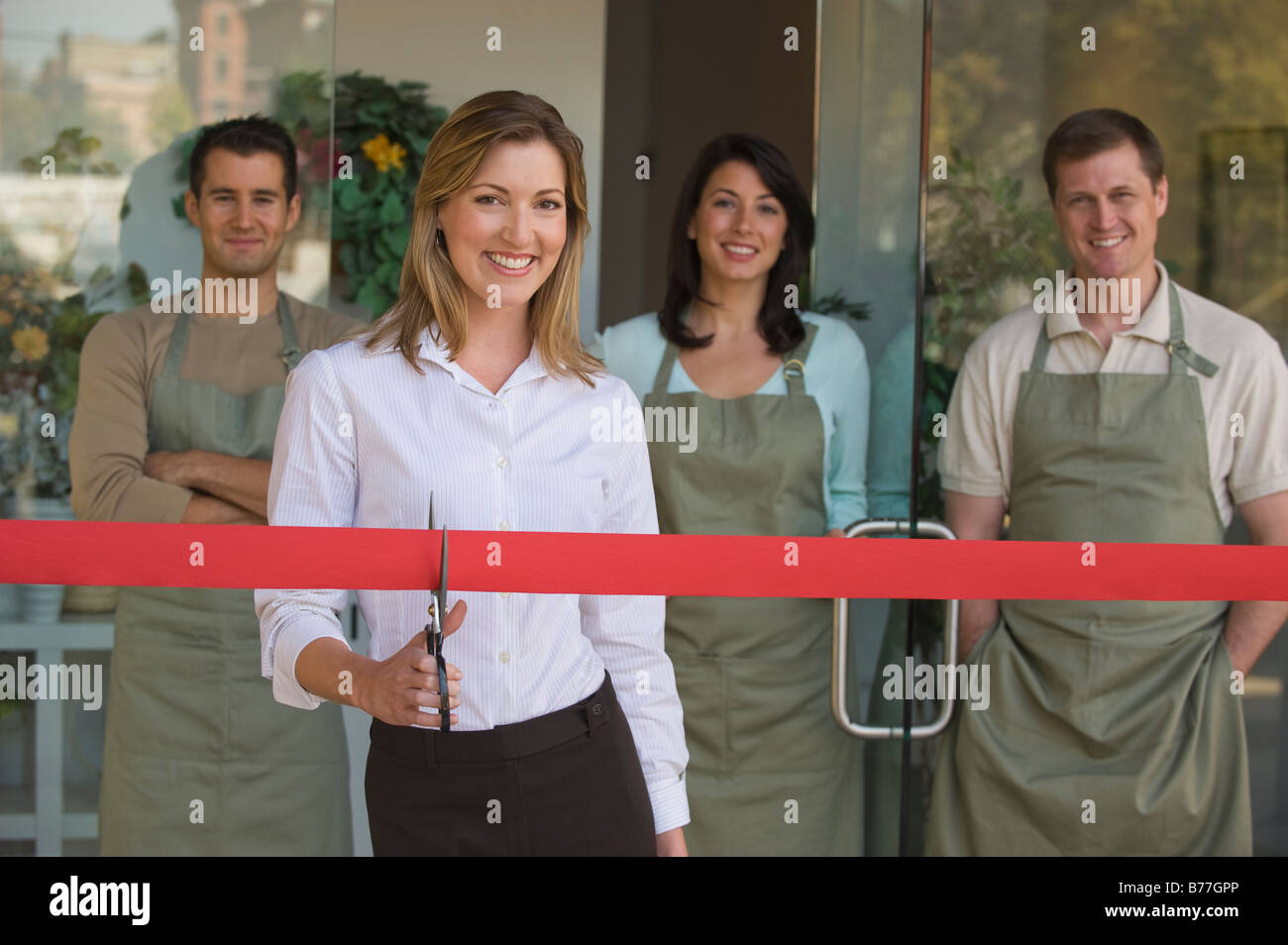 Small business owner cutting red ribbon grand opening - Stock Image