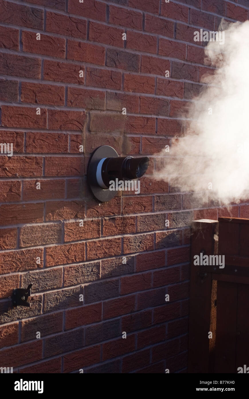 Steam Vapour Extrudes From a Condensing Boiler Exhaust Pipe in a Modern British Home Alsager Cheshire England United - Stock Image