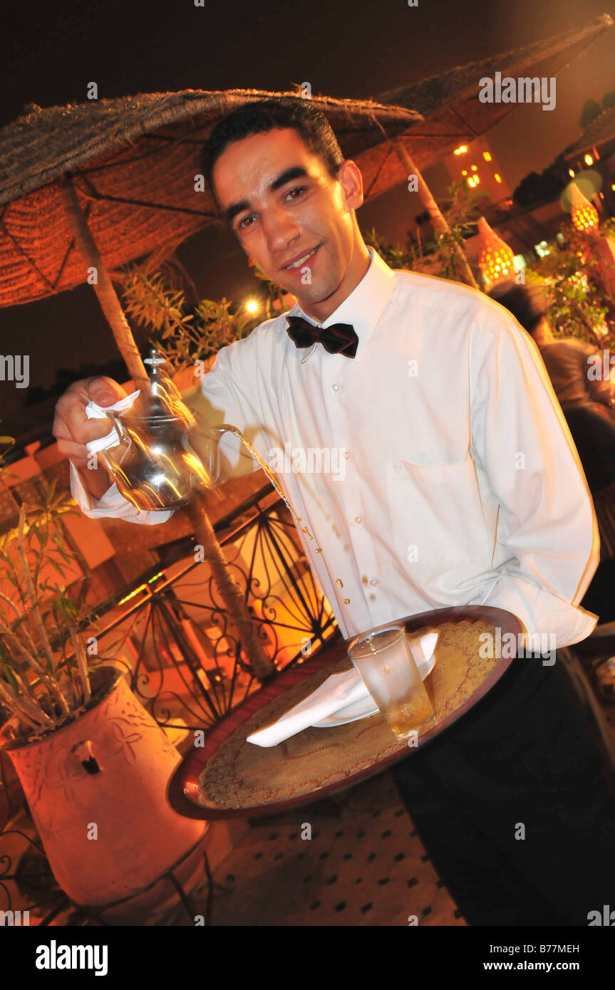 Waiter serving mint-tea, restaurant in the Place Djemma el-Fna, Square of the hanged, imposter square, Marrakech, - Stock Image