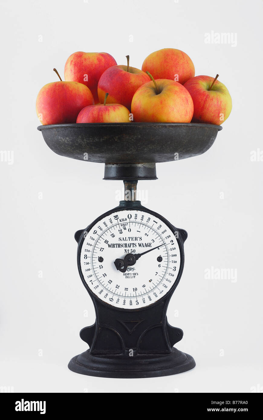 Antique iron kitchen scales with scale pan filled with almost 2 kg of apples - Stock Image