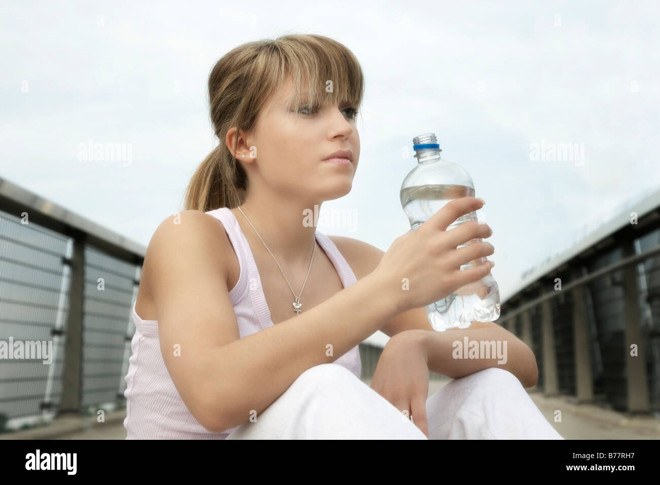 Young woman with a bottle of water quenching her thirst after doing sport - Stock Image