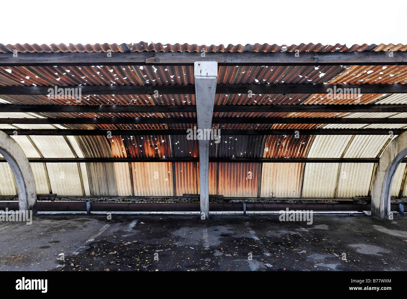 Corrugated roof made of plastic, holes caused by hail, brown colouring caused by factory fumes, factory parking - Stock Image
