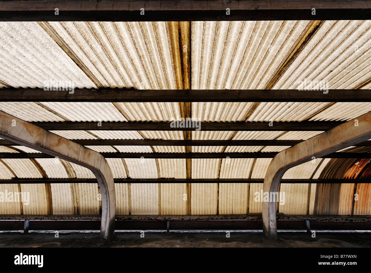 Corrugated roof made of plastic, brown colouring caused by factory fumes, pollution, factory parking place in the - Stock Image