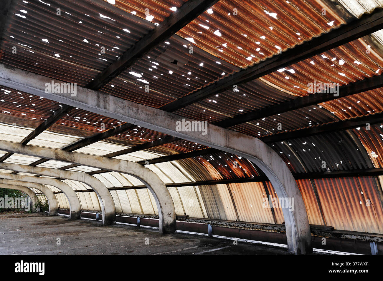 Corrugated roof made of plastic, holes caused by hail, brown colouring caused by pollution, factory parking place - Stock Image