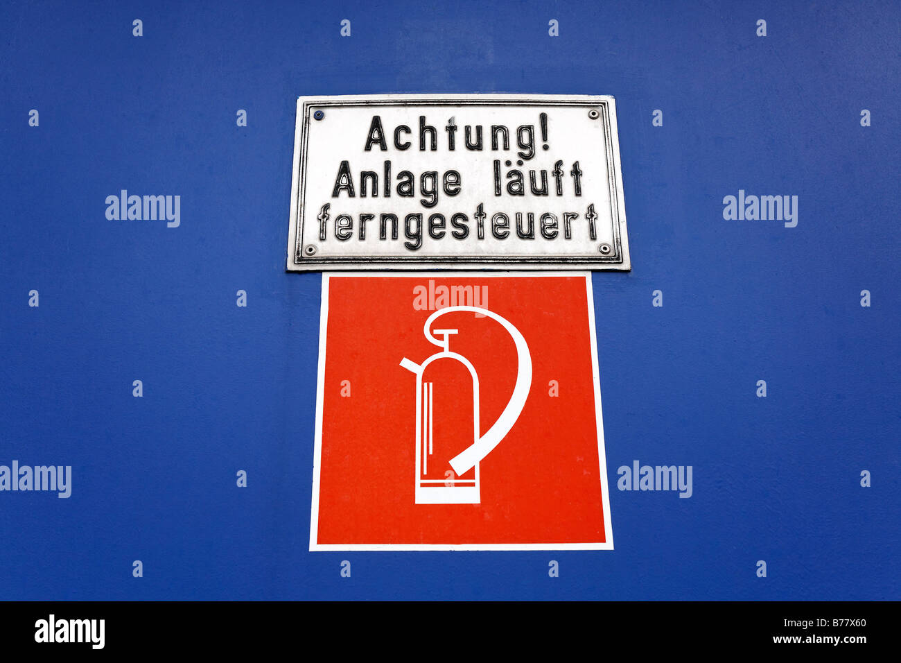 Attention, machines controlled remotely, sign on blue steel door, symbol for fire extinguisher, Duisburg, Ruhr area, - Stock Image