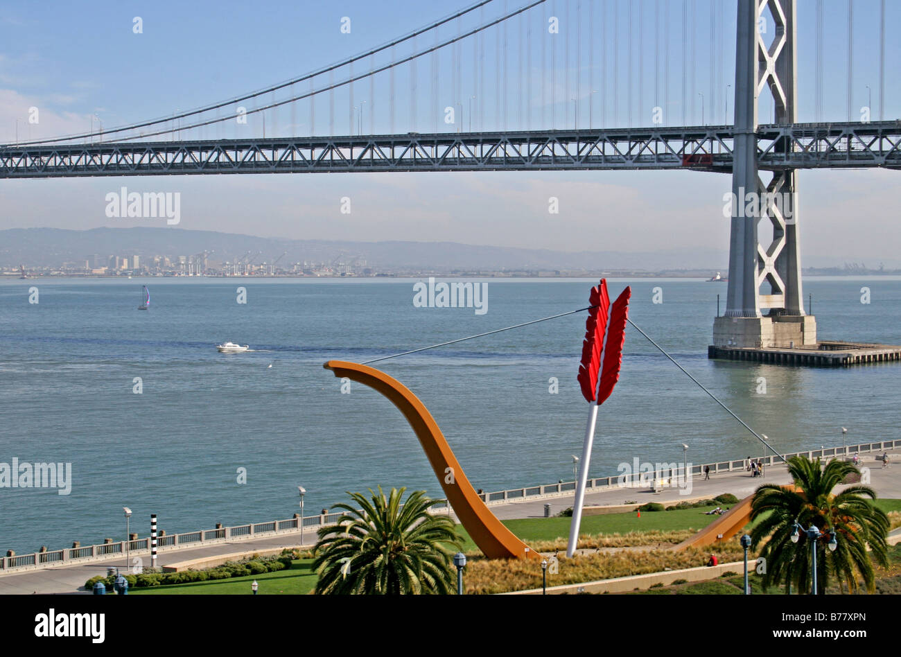 couple riding bikes past Cupid's Span sculpture on The Embarcadero San Francisco California - Stock Image