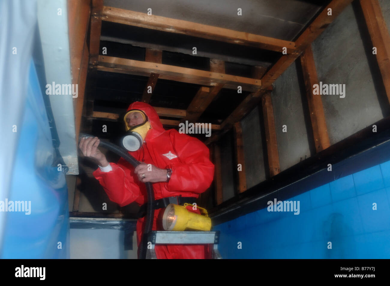 Man in full protective clothing inside a secured environment cleaning up after asbestos removal Exeter - Stock Image