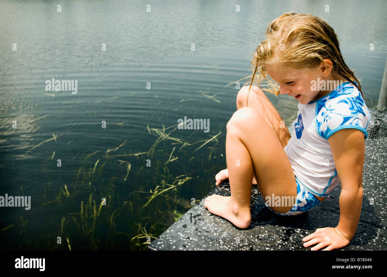 Young girl on dock by lake, Lifestyle - Stock Image