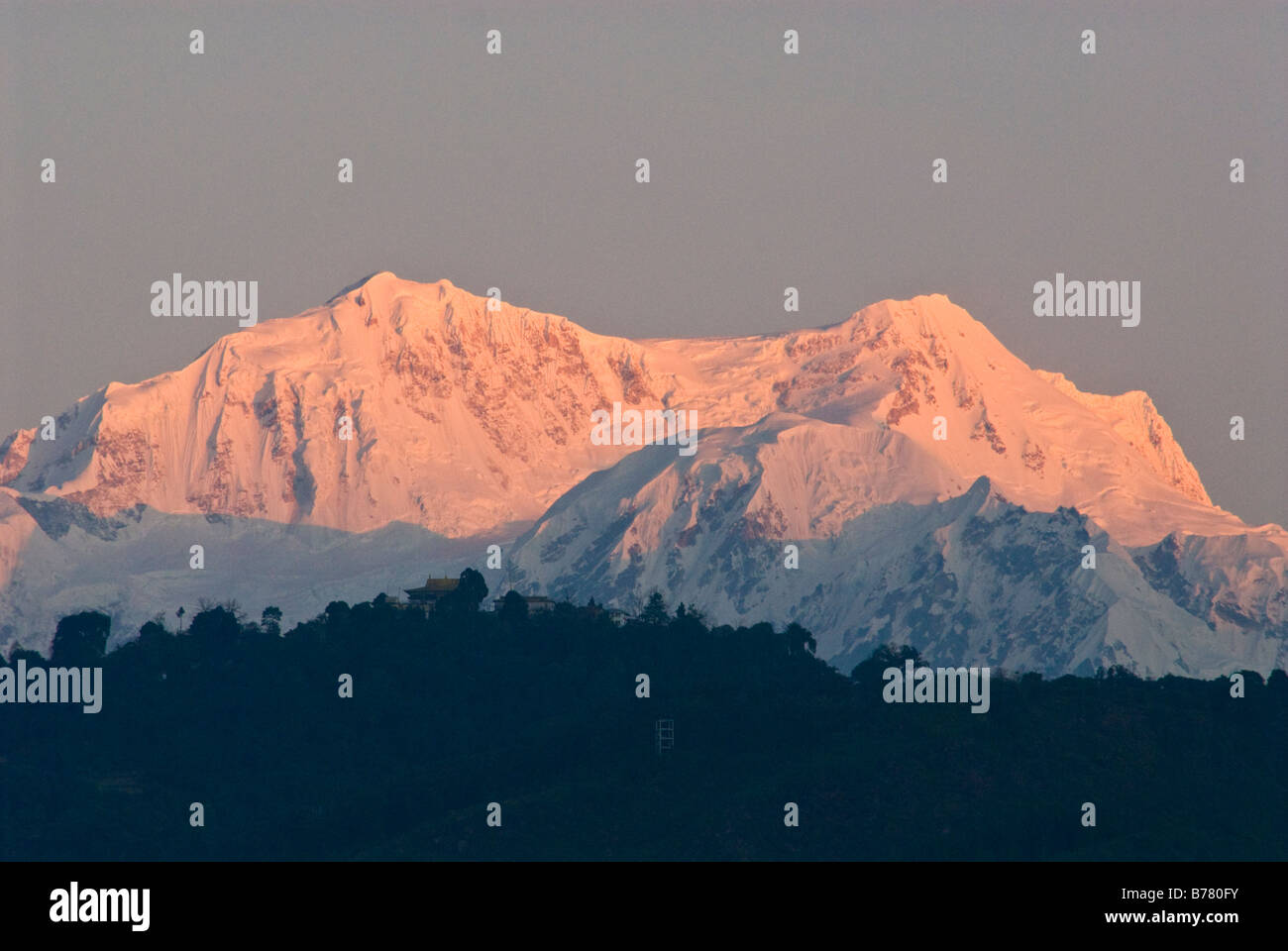 Peaks of the Kangchenjunga mountain range, Sikkim, at dawn. Pemayangtse monastery can be seen on the hilltop in - Stock Image
