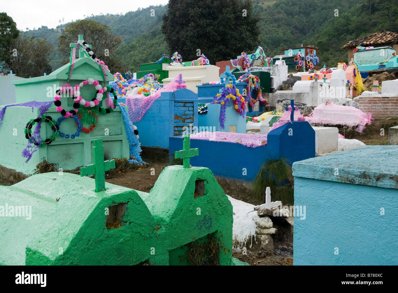 Multi coloured graves on a cemetery decorated with garlands for the 'Day of the Dead' and 'All Souls - Stock Image