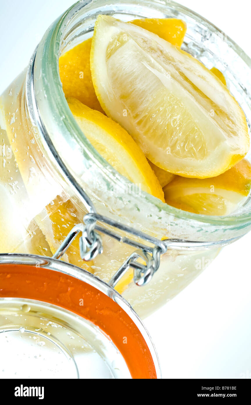 Parfait jar of preserved lemons. Quarters of lemons are covered in salt then topped up with lemon juice. Used in - Stock Image