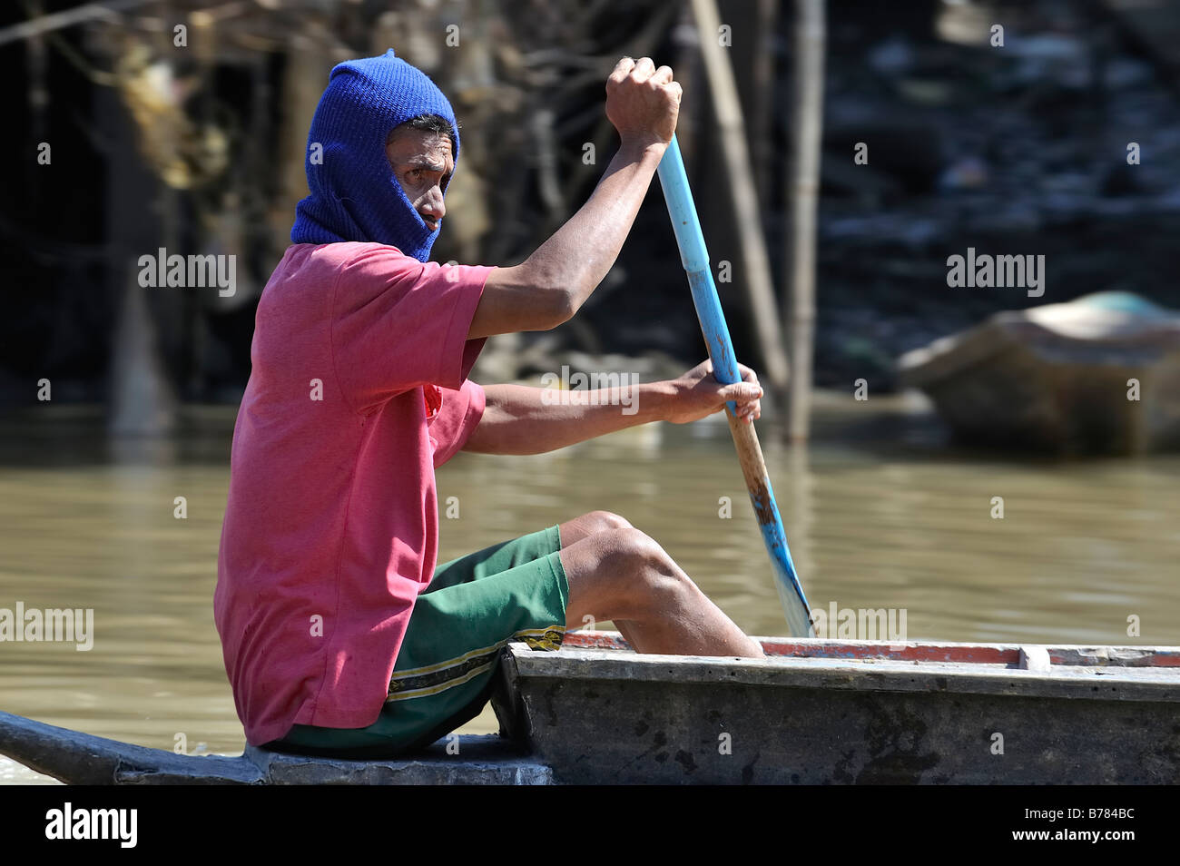 A Thai fisherman on his rowing boat in the Chao Phraya river Stock Photo
