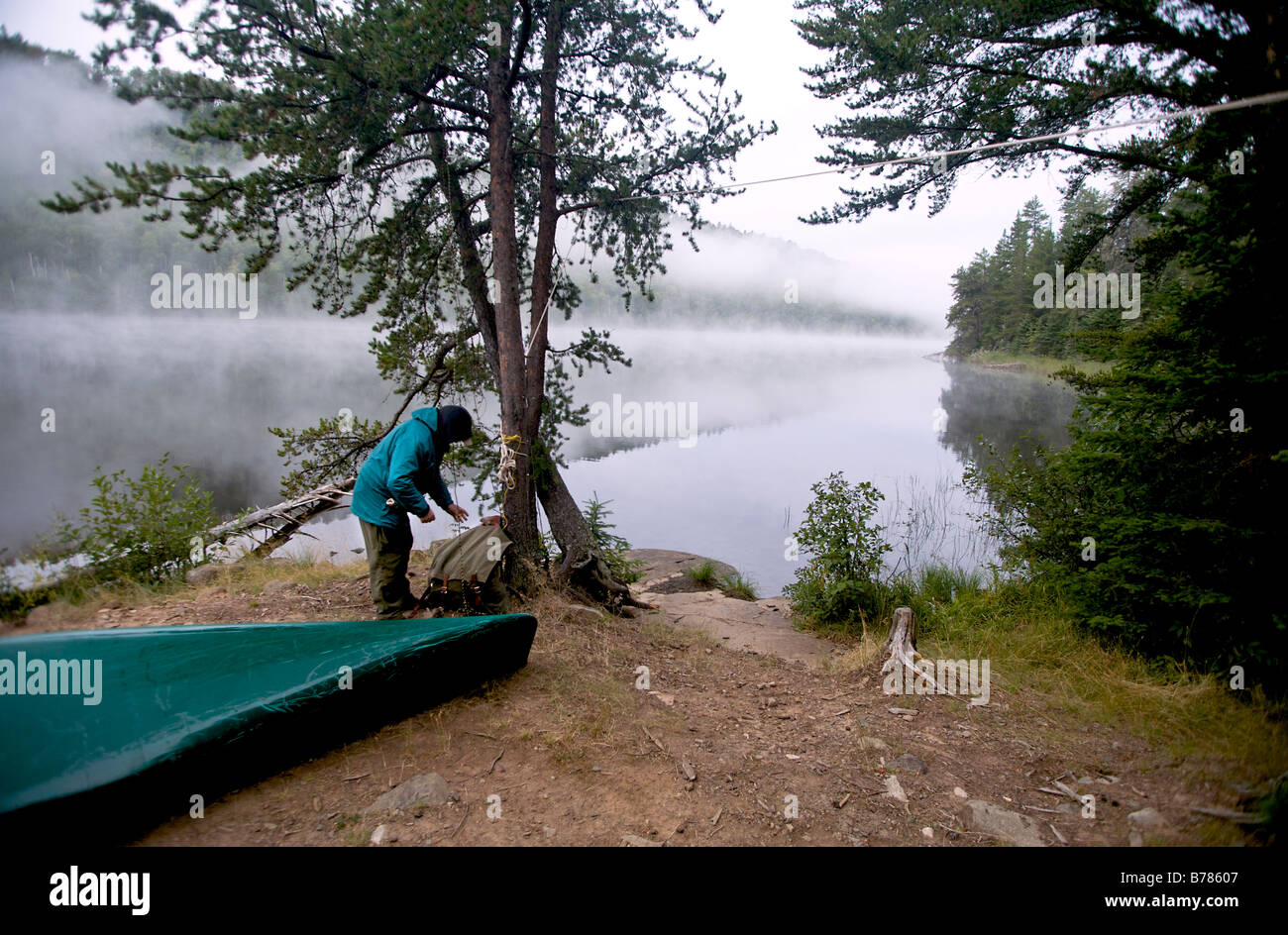 Taking down the food pack that hangs from a tree at base camp in Boundary Waters Canoe Area in Minnesota. - Stock Image