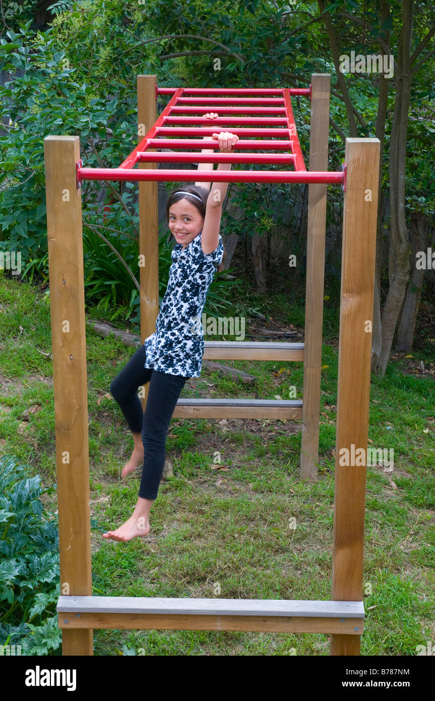 Slim young girl swinging on monkey bars in garden - Stock Image