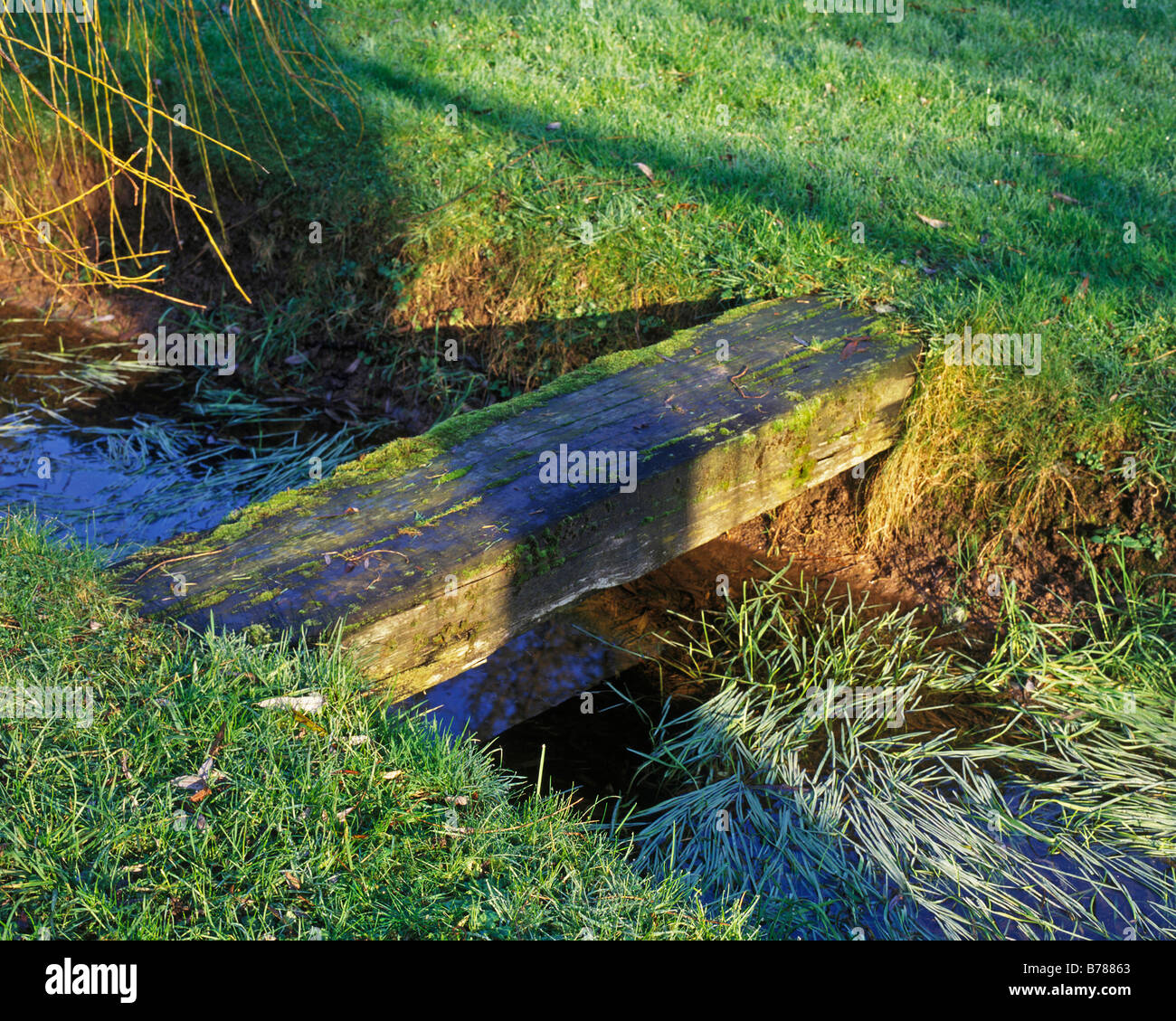 SINGLE RAILWAY SLEEPER FOOTBRIDGE ACROSS GARDEN STREAM - Stock Image