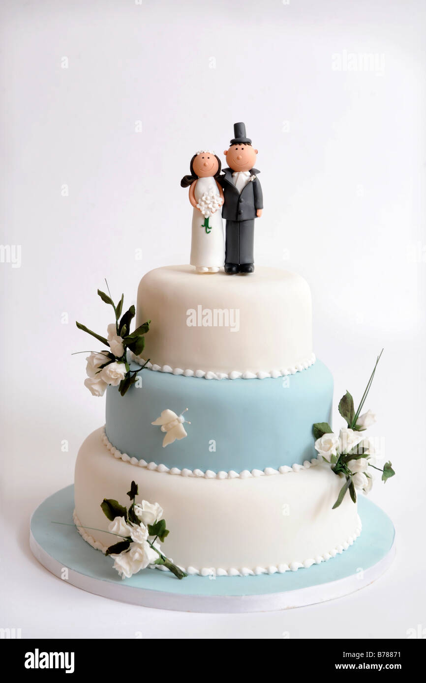 A THREE TIER WEDDING CAKE WITH DECORATIVE FLOWERS AND COMIC BRIDE ...
