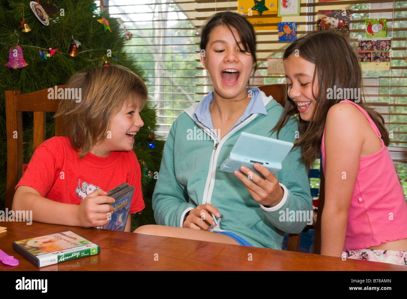 Three young Australian children playing with a new Nintendo DS Lite on Christmas morning - Stock Image