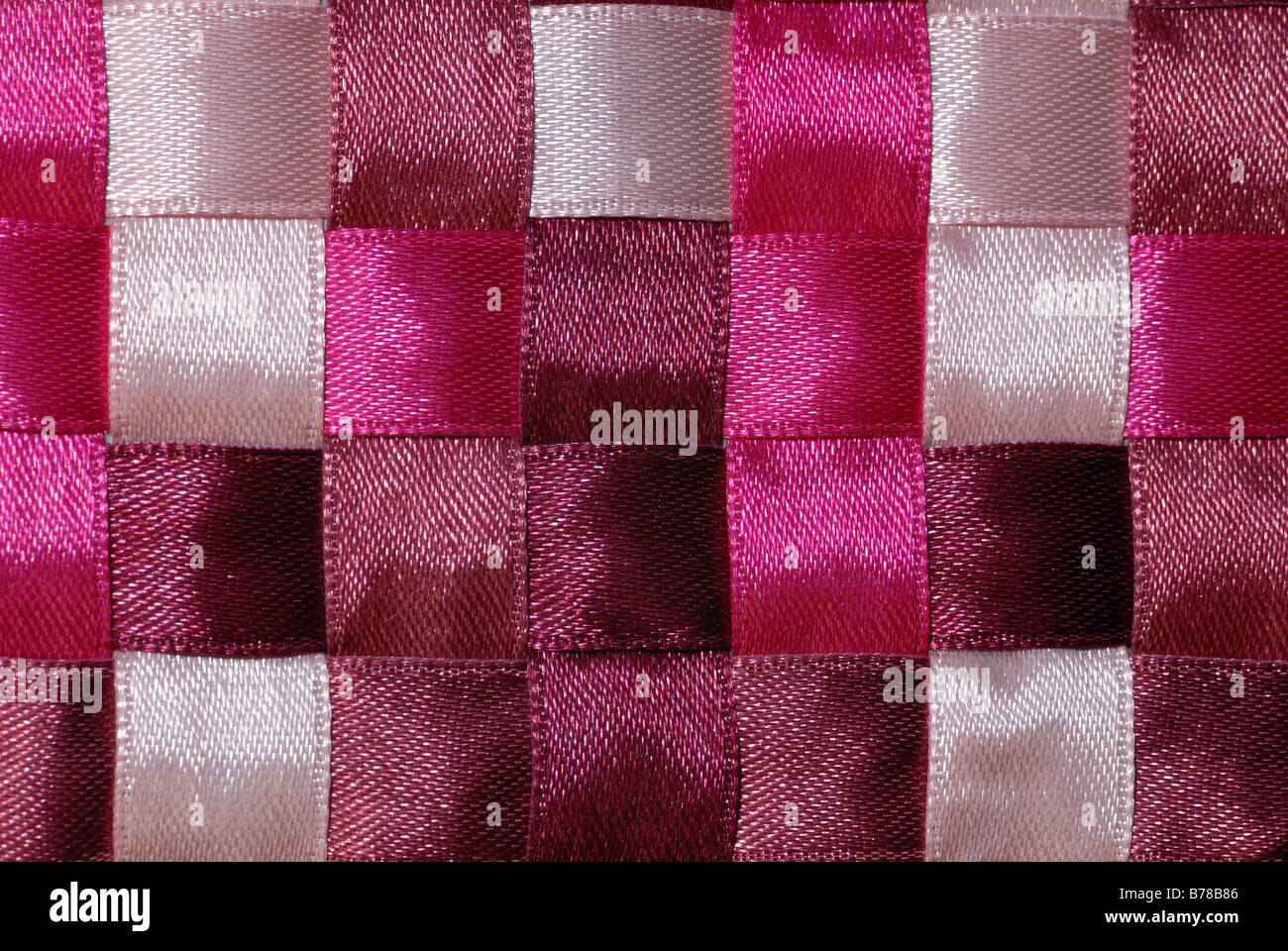 Pink ribbon of varying colors woven into a checkerboard pattern. - Stock Image