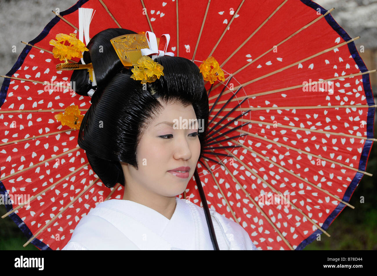 bride wearing a wedding kimono holding a traditional paper parasol