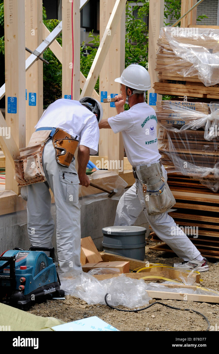 Assembly of a modern prefabricated house in light wooden framework construction, workmen with tools in waistbelts, - Stock Image