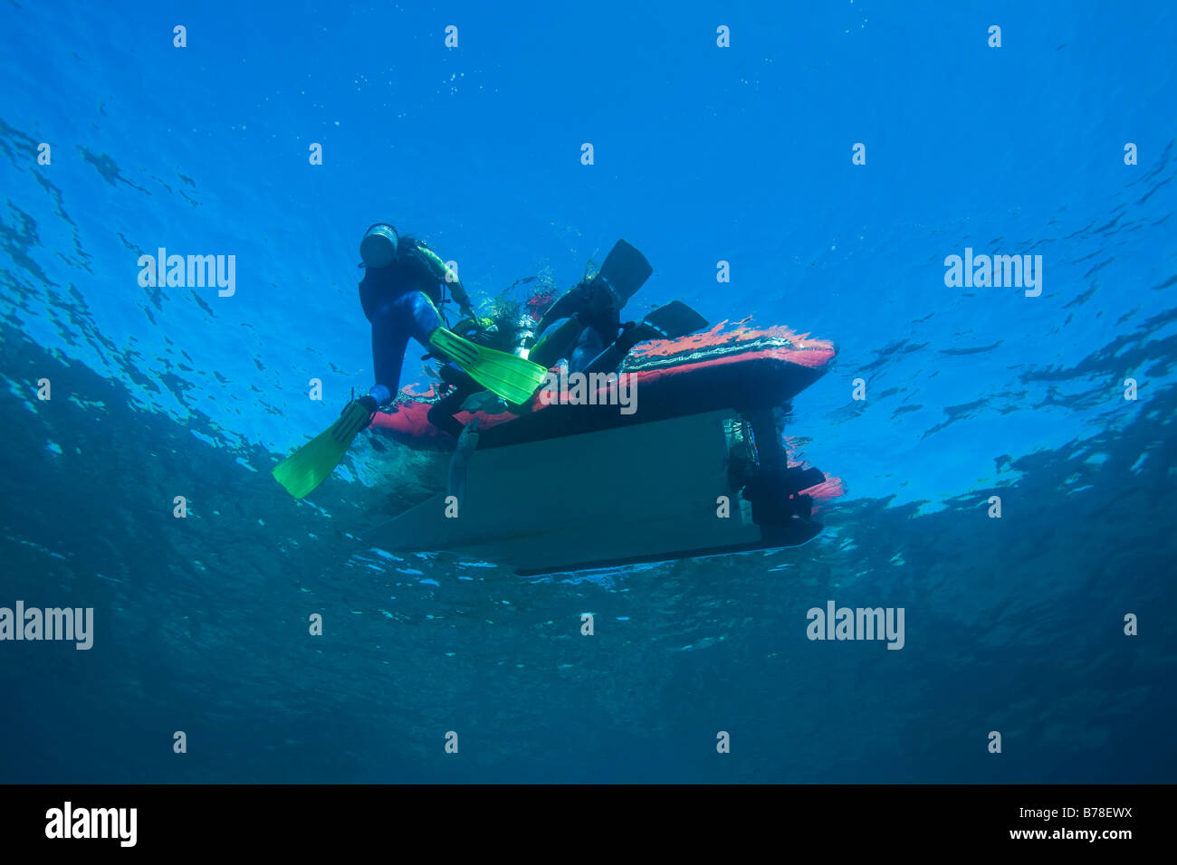 Divers ardously clamber on to the boat after diving, Indonesia, South Asia - Stock Image