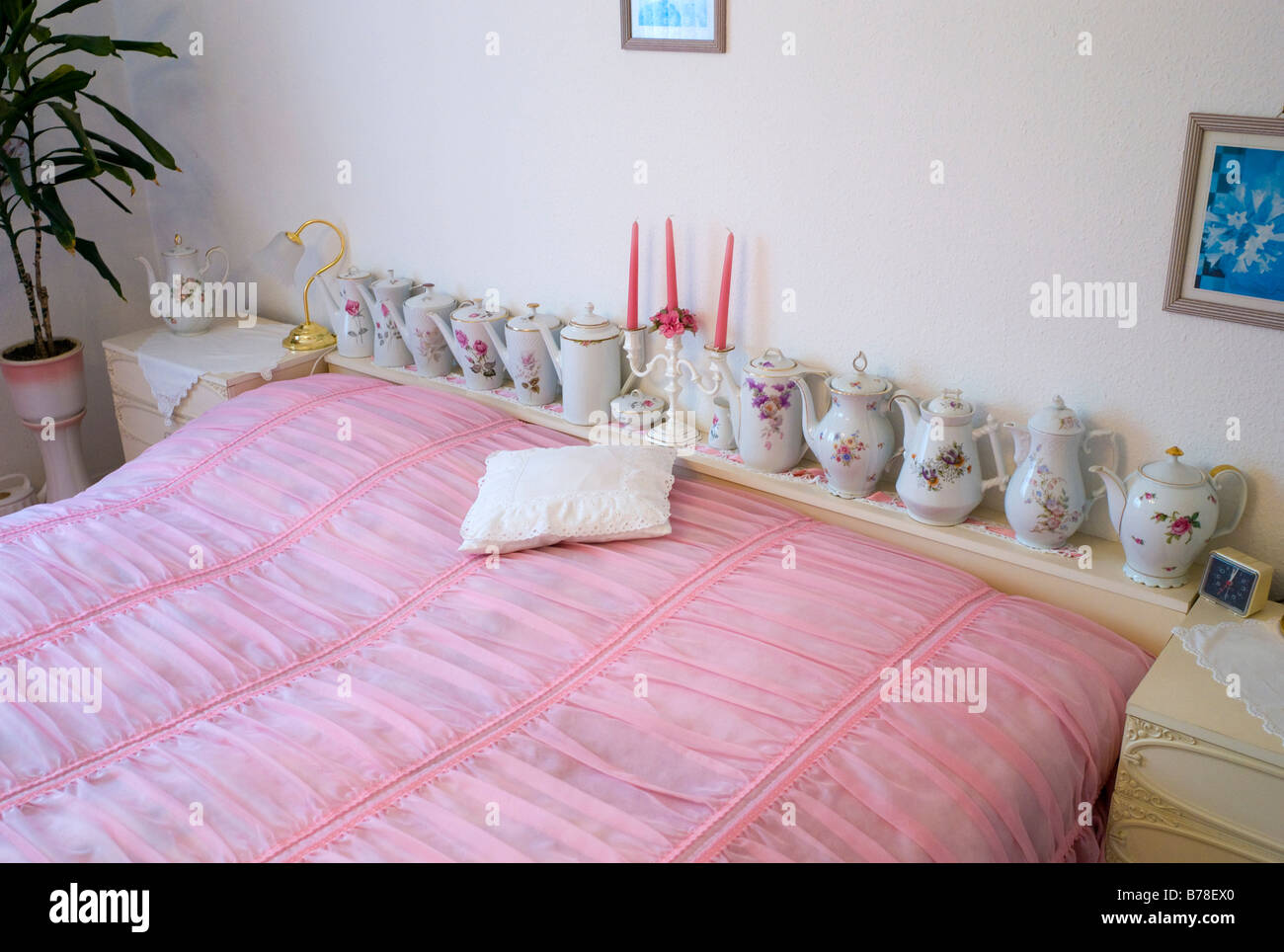 Old fashioned bedroom with pink bedspread and teapots, Germany, Europe Stock Photo