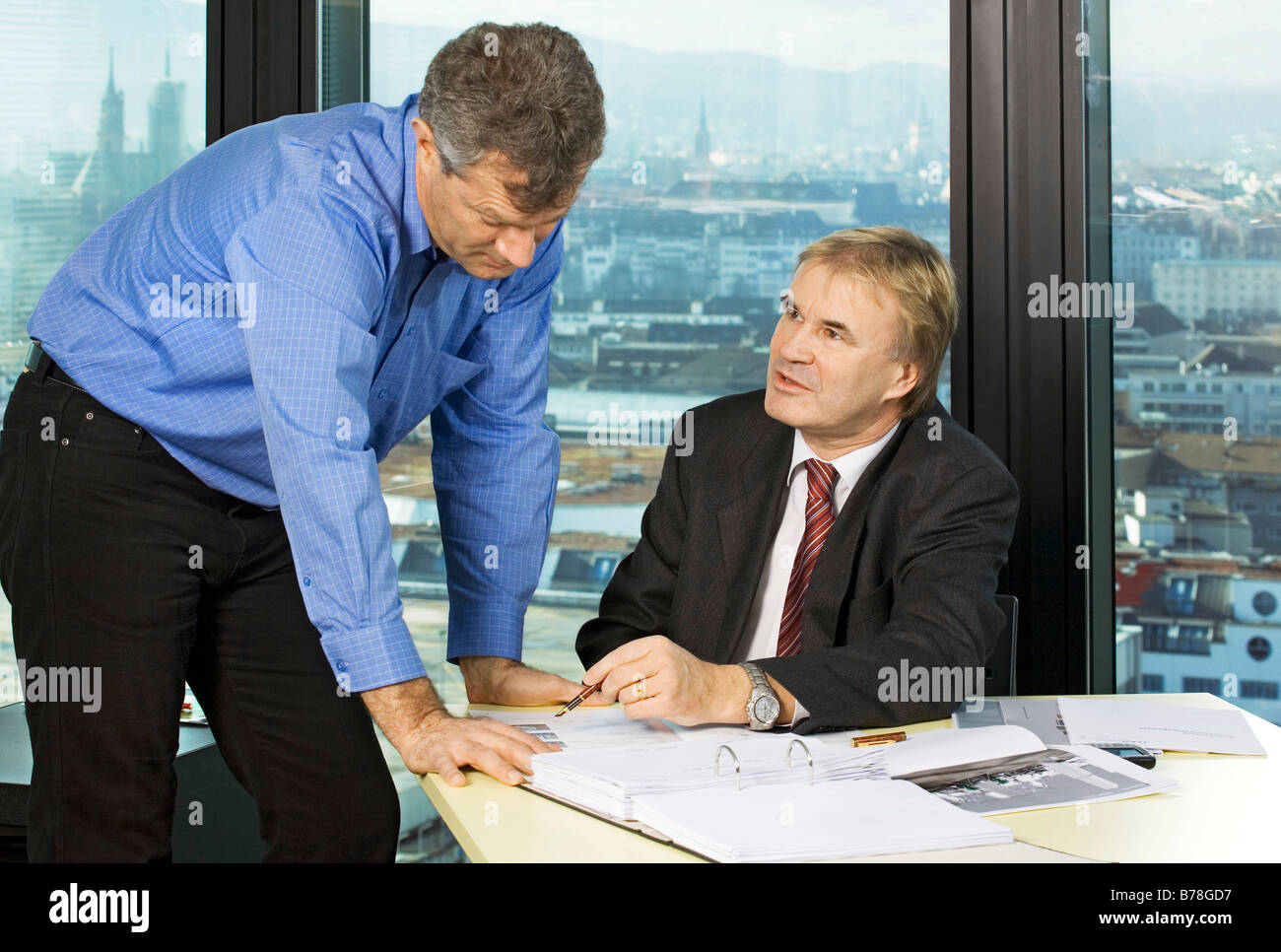 Department manager and office manager of Messe Schweiz, Swiss Exhibition, discussing in an office of the exhibition - Stock Image