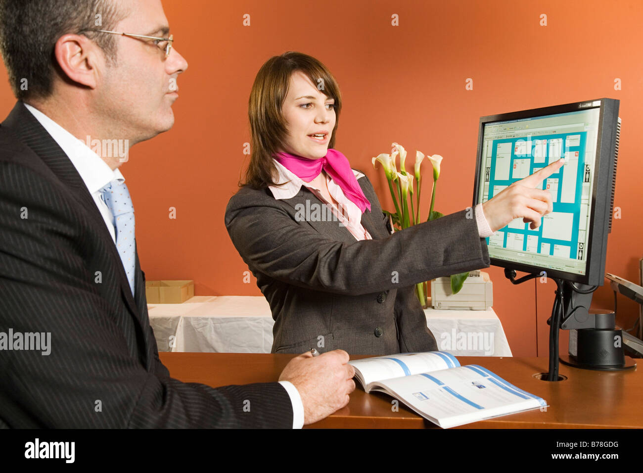 Hostess of Messe Schweiz explaining to a visitor on the screen the way to an exhibition booth in the Basel Exhibition - Stock Image