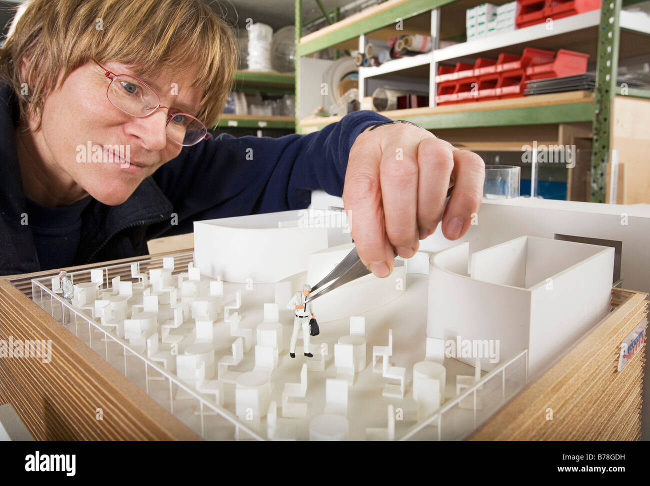 Model builder for the Expomobilia company which constructs exhibition booths placing a model figure in the model - Stock Image