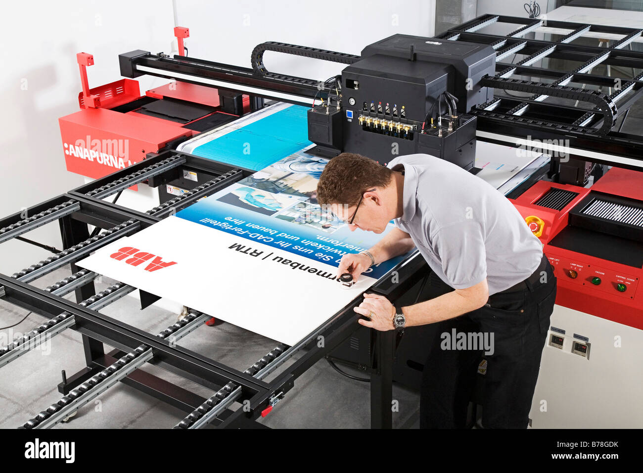Printer for the Expomobilia company which constructs exhibition booths during quality control and checking a printed - Stock Image